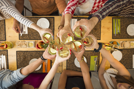 Group of people toasting and looking happy at a restaurant Фото со стока