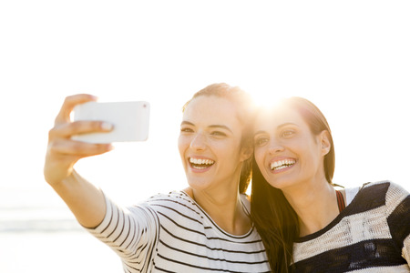 Two best friends taking a selfie with cellphone Фото со стока