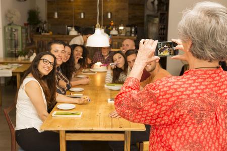 おばあちゃんの誕生日の祖父を祝っているすべての家族の写真を撮る