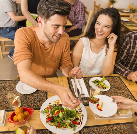 Pareja feliz en el restaurante y se sirve de la comida en el plato Foto de archivo - 43054191