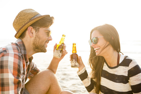 Young couple at the beach having fun, laughing and drinking beer 免版税图像