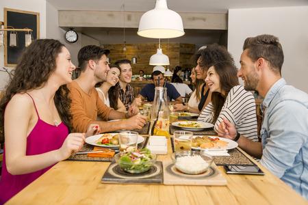 Grupo multiétnico de amigos felices que almuerzan y divertirse en el restaurante Foto de archivo - 43054207