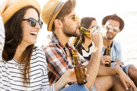 ビーチで一緒に楽しんで、冷たいビールを飲む友人