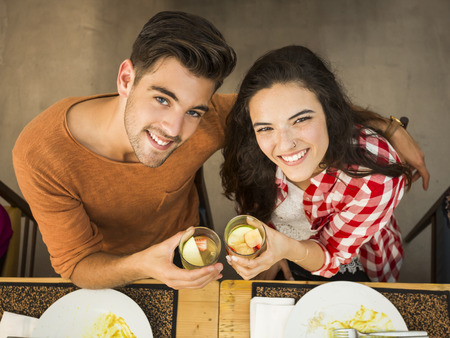 Young couple toasting and looking happy at a restaurant