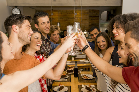 Group of friends toasting and looking happy at a restaurant Stock Photo