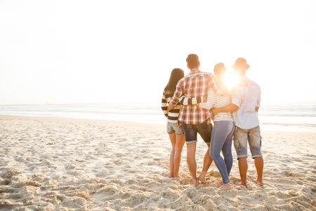 Grupo de amigos en la playa y ver el atardecer Foto de archivo - 43061700