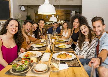 Multi-etnische groep van gelukkige vrienden lunchen en het maken van een selfie Stockfoto
