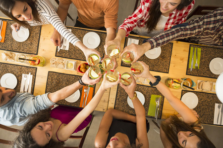 Group of people toasting and looking happy at a restaurant Standard-Bild