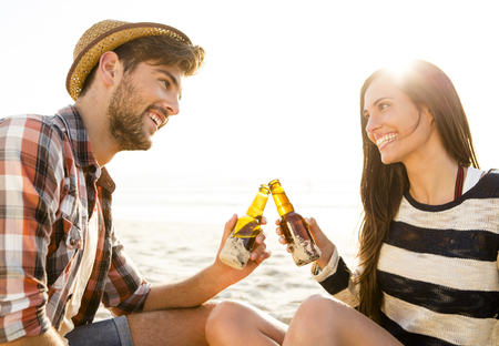 Young couple at the beach having fun, laughing and drinking beer Stock Photo