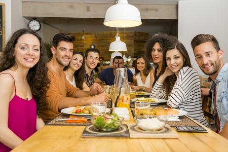 Multi-etnische groep van gelukkige vrienden lunchen en plezier in het restaurant