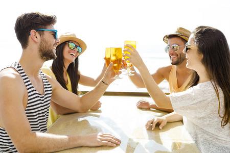 Amigos que se divierten y beber una cerveza fría en el bar de la playa Foto de archivo - 43064004