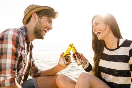 楽しんで、笑って、ビールを飲みながらビーチで若いカップル