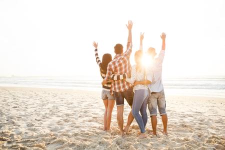 Groep vrienden op het strand en kijken naar de zonsondergang