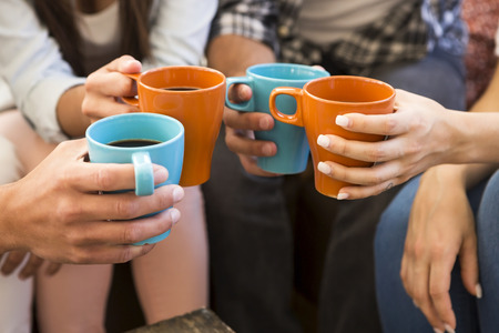 Group of friends making a toast with coffee