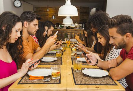 테이블에있는 모든 사람들과 레스토랑에서 친구의 그룹은 휴대폰 점유