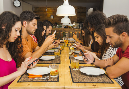 Group of friends at a restaurant with all people on the table occupied with cellphones Reklamní fotografie - 44307235