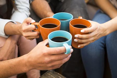 Groep vrienden die een toost met koffie Stockfoto
