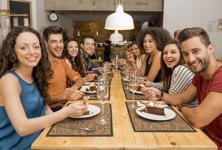 Multi-etnische groep van gelukkige vrienden lunchen en proeven van het dessert in het restaurant Stockfoto
