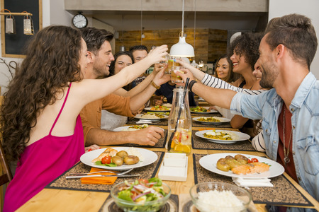 Group of friends toasting and having a good time at the restaurant