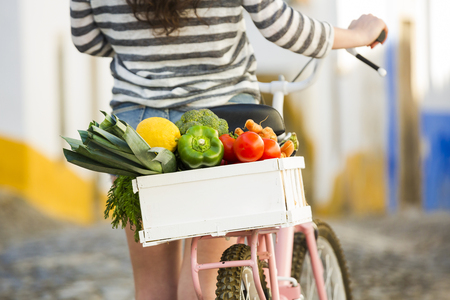 Beautiful female tourist living like a local, with her bicycle after buying some fresh vegetables Imagens - 43816862