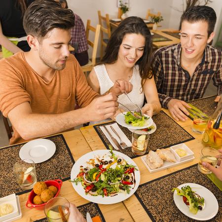 レストランでは、プレートの食品の提供されている友人