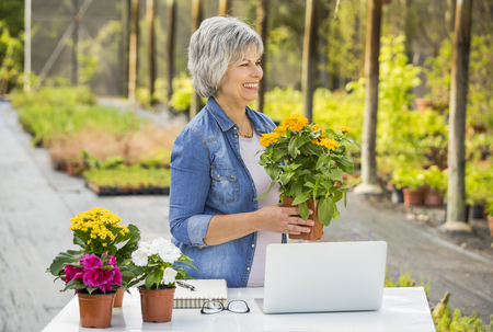Beautiful Mature Woman Working In A Greenhouse Holding Flowers ... on beautiful floral design, beautiful timeline design, beautiful building design, beautiful industrial design, beautiful yard design, beautiful greenhouse structure, beautiful fish design, beautiful furniture design, beautiful garden design, beautiful bar design, beautiful family design, beautiful gift shop design, beautiful greenhouse garden, beautiful nature design, beautiful home greenhouse, beautiful greenhouse interiors, beautiful small greenhouses, beautiful hospital design, my garden layout design, beautiful solar design,