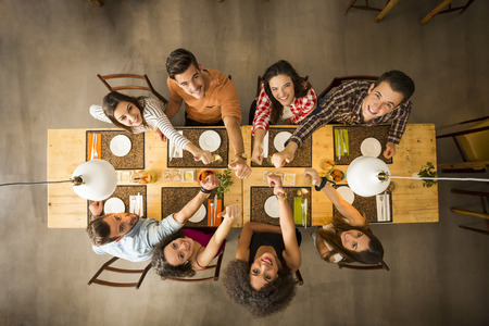 Group of people toasting and looking happy at a restaurant Archivio Fotografico
