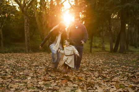 Outdoor portrait of a happy family enjoying the fall season Stock Photo