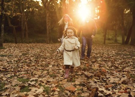 秋のシーズンを楽しんで幸せな家族の屋外のポートレート