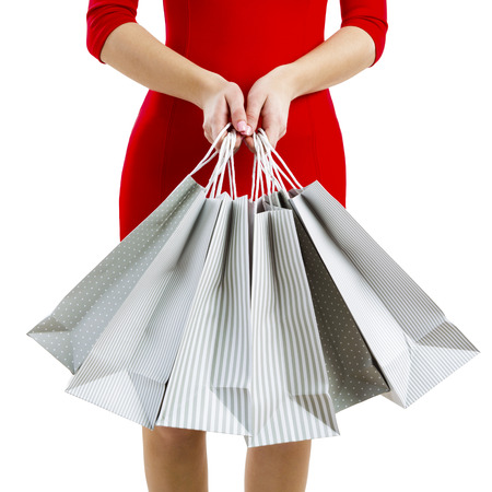Mooie en aantrekkelijke vrouw met een sexy jurk bedrijf boodschappentassen