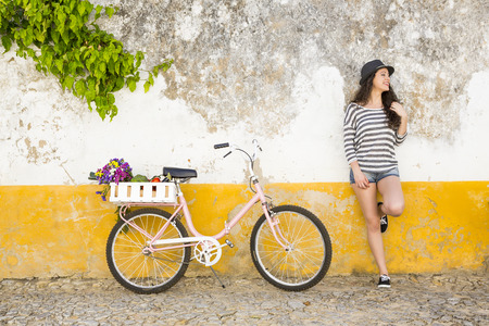 Female tourist living like a local, with her bicycle after buying fresh vegetables