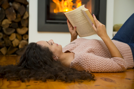 Beautiful woman reading a book at the warmth of the fireplace Stock Photo