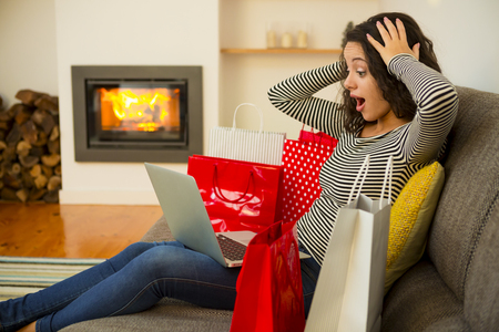 Beautiful woman at home at the warmth of the fireplace, shopping online Stockfoto