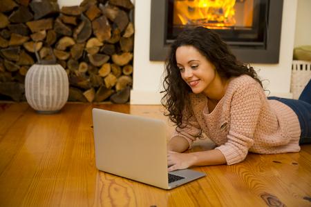 Belle femme travaillant avec un ordinateur portable à la chaleur de la cheminée Banque d'images - 46913875
