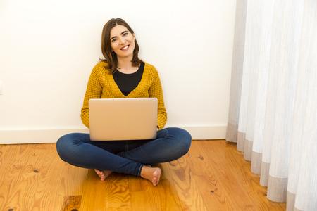 Belle femme assise sur le plancher de travail sur l'ordinateur portable Banque d'images - 46914122