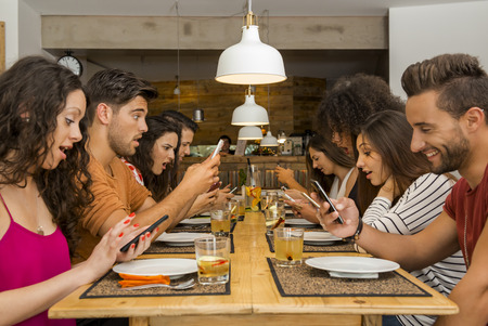 Group of friends at a restaurant with all people on the table occupied with cellphones Stok Fotoğraf - 48153693
