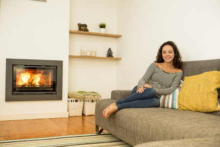 Beautiful woman in the living room at the warmth of the fireplace Stock Photo