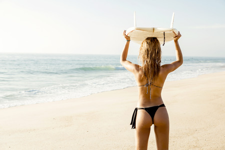 Beautiful young girl holding a surfboard and checking the waves