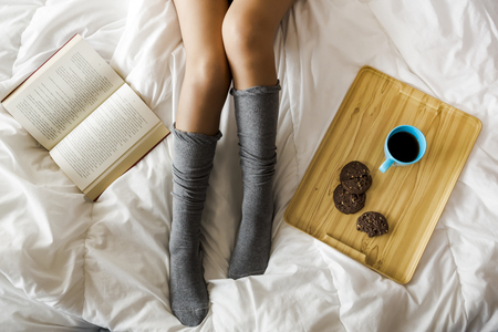 Woman on bed drinking a coffee with cookies