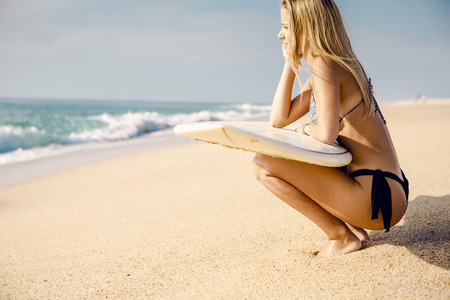 Beautiful and sexy surfer girl holding a surfboard and checking the waves