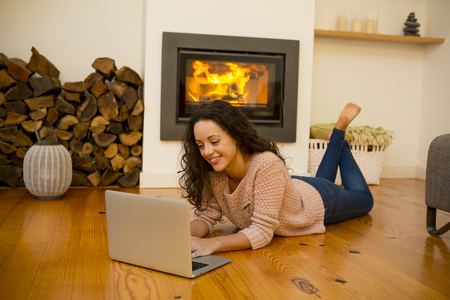 Beautiful woman working with a laptop at the warmth of the fireplace