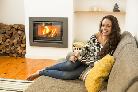 Beautiful woman in the living room at the warmth of the fireplace Archivio Fotografico