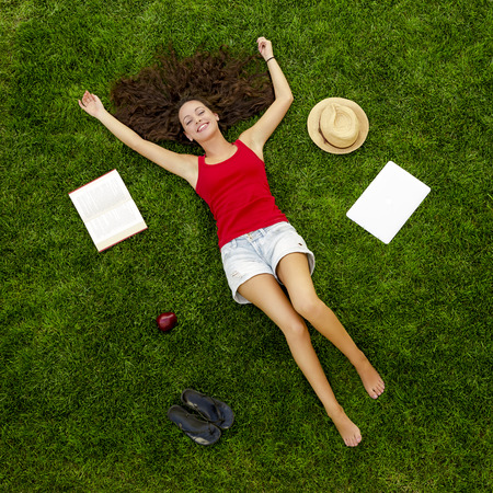 草の上に横たわる美しい、幸せな若い女性