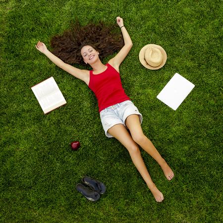 잔디에 누워 아름답고 행복한 젊은 여자