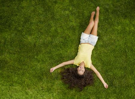 草の上に横たわる美しい若い女性の屋外のポートレート