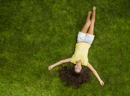 Outdoor portrait of a beautiful young woman lying on the grass
