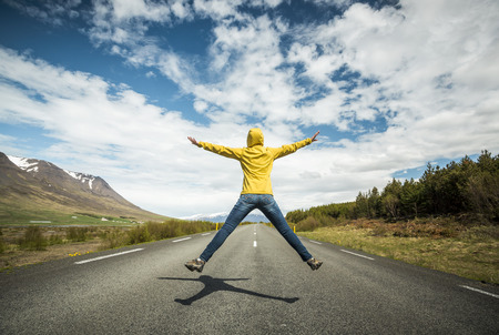 Woman jumping on a beautiful road Imagens