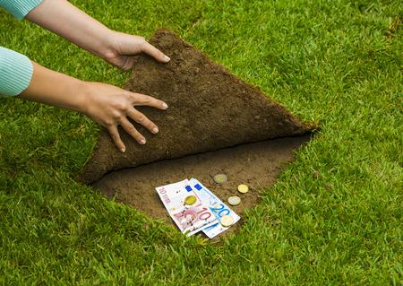 Finances concept, hands hiding money under the grass Stockfoto