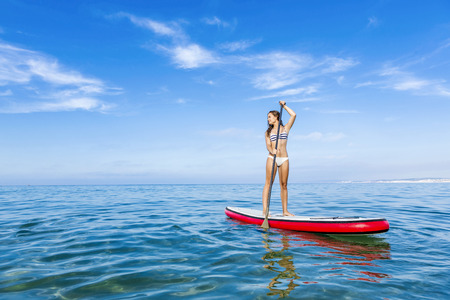A beautiful woman practicing paddle on a beautiful sunny day Stock Photo