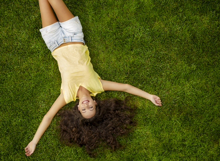 Retrato al aire libre de una hermosa mujer joven tumbado en la hierba